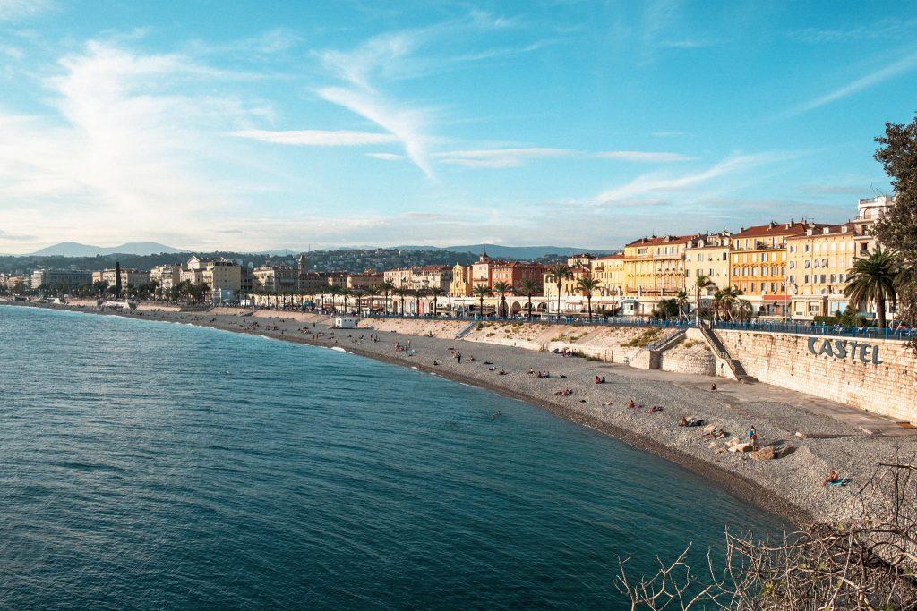 Panorama Aufnahme von Nizzas Strand mit Häusern und Hügeln im Hintergrund